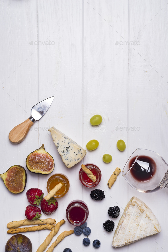 Different types of cheeses with wine glass and fruits - Stock Photo - Images