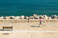 Woman jogging on city street at seaside