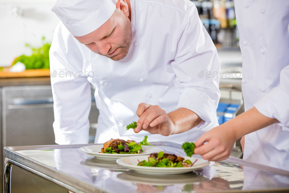 Two dedicated chefs prepares steak dish at gourmet restaurant - Stock Photo - Images
