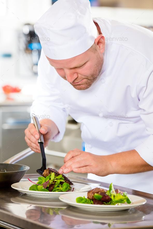 Chef prepares steak dish at gourmet restaurant - Stock Photo - Images
