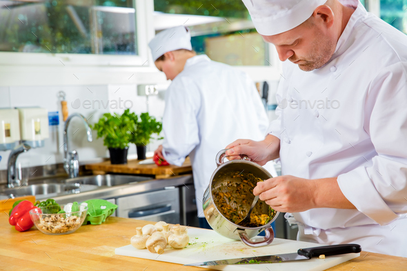 Professional chefs makes food dishes in large kitchen - Stock Photo - Images