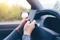 Woman simultaneously driving car and typing text message