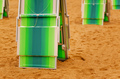 Folded deck chairs at sandy beach at seaside