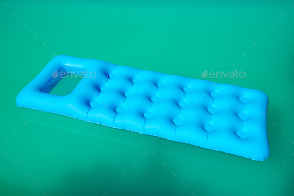 Inflatable mattress floating on swimming pool surface - Stock Photo - Images