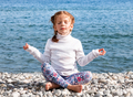 A little girl sitting on a pebble beach, practicing yoga and meditating. - PhotoDune Item for Sale