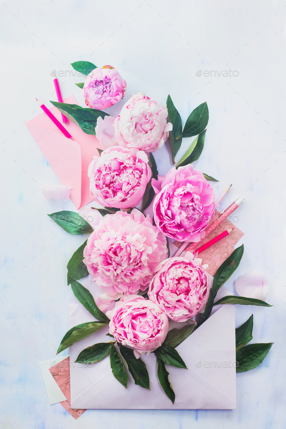 Envelope full of pink flowers with pencils and notes on a light background - Stock Photo - Images