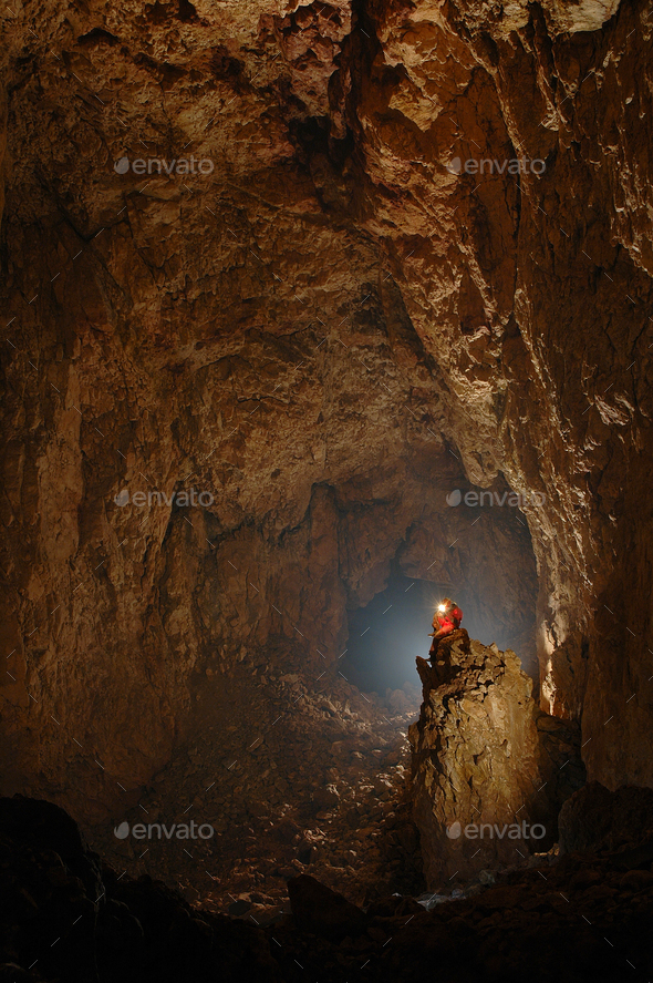 Monumental cave chamber with a spelunker - Stock Photo - Images