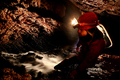 Spelunker exploring underground river in a cave