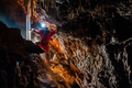 Spelunker discovering water underground in a cave - PhotoDune Item for Sale