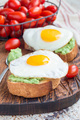 Open sandwiches with mashed avocado and fried egg, vertical