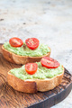 Open sandwiches with mashed avocado and cherry tomatoes, vertical, copy space
