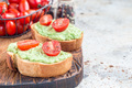 Open sandwiches with mashed avocado and cherry tomatoes, horizontal, copy space