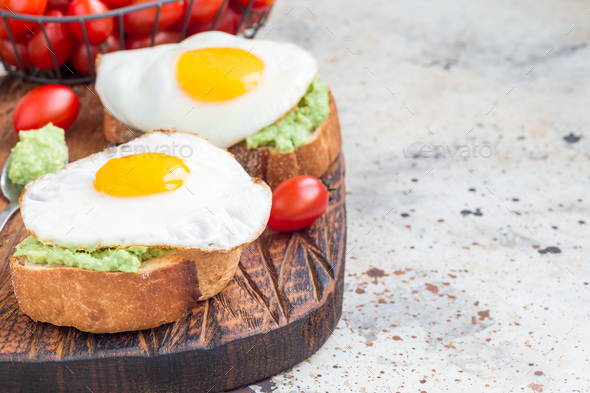 Open sandwiches with mashed avocado and fried egg on a toasted bread, horizontal, copy space - Stock Photo - Images