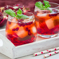 Mojito cocktail with pomegranate, mint, lemon juice and ice in glass, square