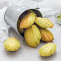 Matcha green tea madeleines on table and in metal bucket, square