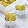 Matcha green tea madeleines on table and in wooden tray, square