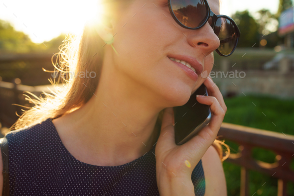 Woman in sunglasses talking on the smartphone while walking down - Stock Photo - Images