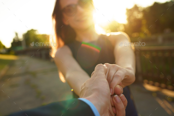 Follow me - happy young woman pulling guy's hand - hand in hand - Stock Photo - Images
