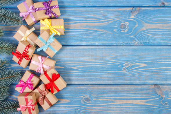 Gifts with ribbons for Christmas and spruce branches, copy space for text on old blue plank - Stock Photo - Images