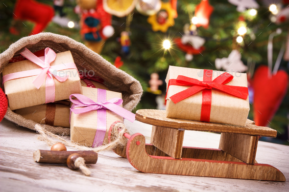 Gifts for Christmas on wooden sled and in bag on background of christmas tree with decoration - Stock Photo - Images