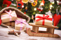 Gifts for Christmas on wooden sled and in bag on background of christmas tree with decoration
