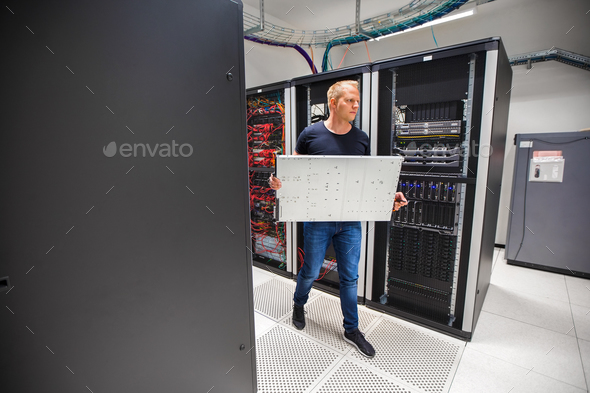 IT Consultant Carrying Blade Server While Walking In Datacenter - Stock Photo - Images