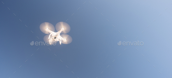 White UAV Quadcopter Drone in Flight Blue Sky - Stock Photo - Images