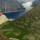 Norway. Guy and Girl Sitting on the Edge of the Trolltunga - VideoHive Item for Sale
