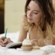 Charming Woman Dressed in Sleepwear Is Writing Something Down Her Notebook with Cup of Coffee and - VideoHive Item for Sale