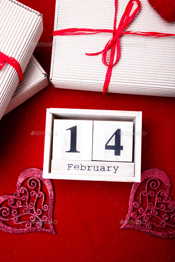 Wooden calendar show of February 14 with red heart and gift boxes. - Stock Photo - Images