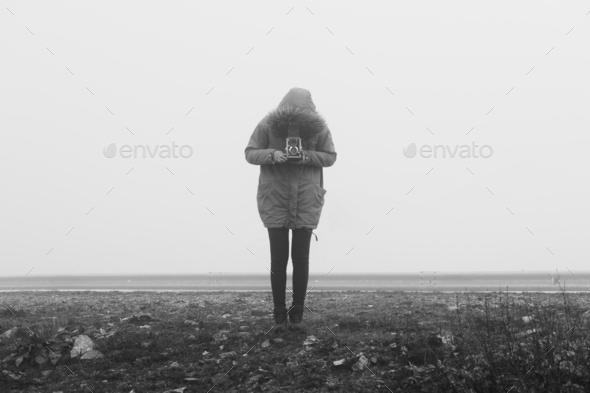 Woman with retro camera in a fog landscape - Stock Photo - Images