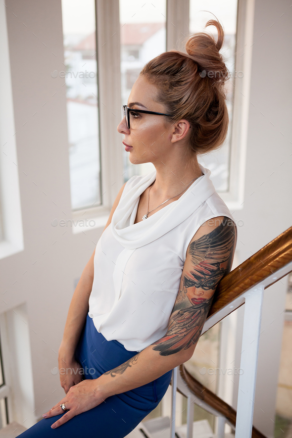 Sexy blonde business woman with a tattoo on her hand - Stock Photo - Images