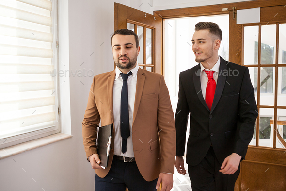 Business partners in formal suit walking and talking - Stock Photo - Images