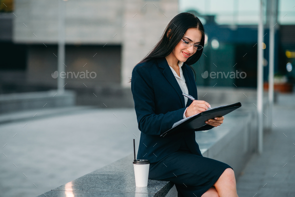 Businesswoman in suit writing in notebook outdoor - Stock Photo - Images