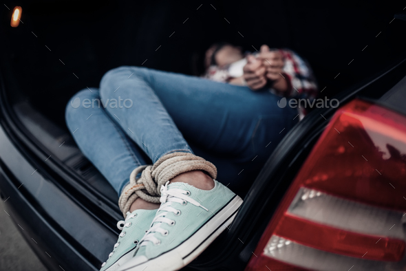 Female victim in car trunk, maniac concept - Stock Photo - Images