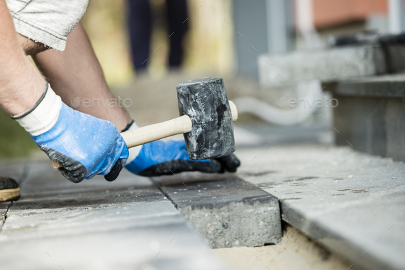 Workman laying a paving stone or brick - Stock Photo - Images