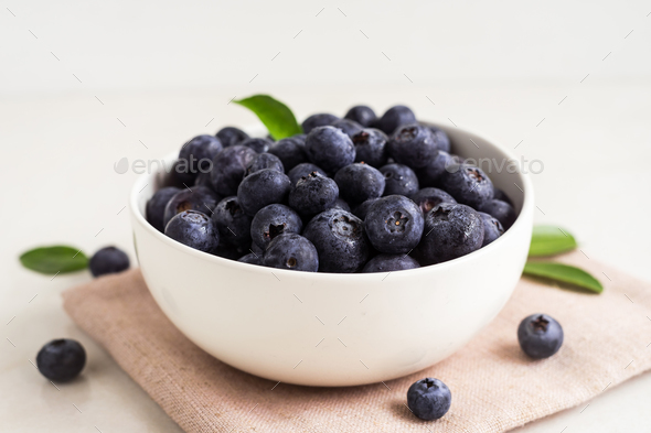 Juicy and fresh blueberries with green leaves on white bowl. Healthy eating - Stock Photo - Images