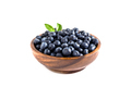 Juicy and fresh blueberries with green leaves on white bowl. Healthy eating