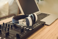 headphones with sound mixer console in home recording studio