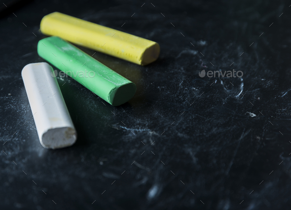 Black old empty chalkboard for copy space with colorful pieces of chalk. Blackboard with chalks - Stock Photo - Images