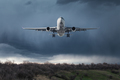 White passenger airplane is flying in the sky with clouds - PhotoDune Item for Sale