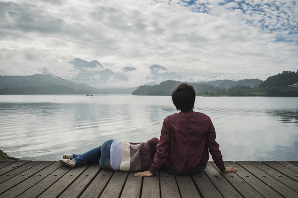 Young couple sitting on wooden pier and looking view of nature - Stock Photo - Images