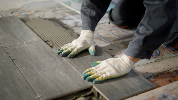 Tiler Is Installing Ceramic Floor Tiles Above Cement And Electric