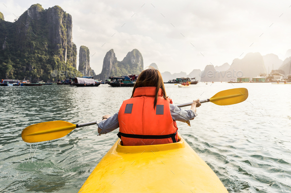 Young woman traveler paddling the kayak in the tropical bay - Stock Photo - Images