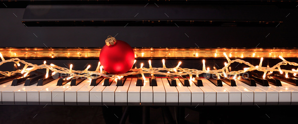 Christmas ball and lights on a piano keyboard, front view - Stock Photo - Images