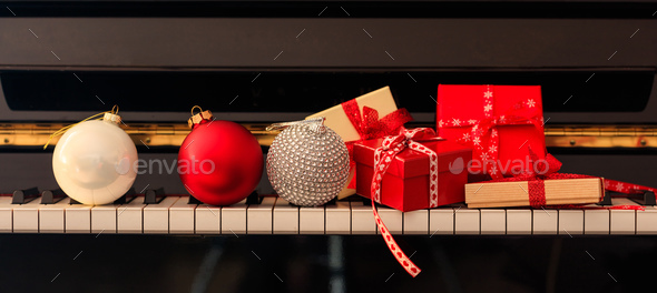 Chritmas balls and gift boxes on piano keyboard, front view - Stock Photo - Images