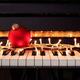 Christmas ball and lights on a piano keyboard, front view