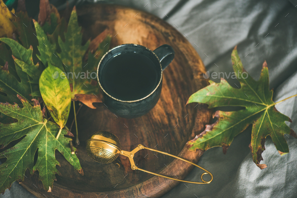Mug of tea with sieve and colofrul autumn leaves - Stock Photo - Images