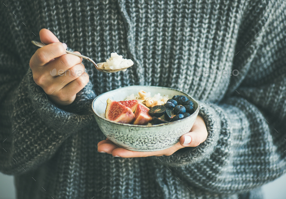 Woman in woolen sweater eating rice coconut porridge - Stock Photo - Images