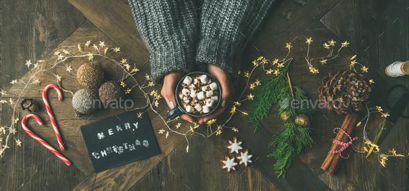 Flat-lay of greeting card, garland, woman's hands holding mug - Stock Photo - Images